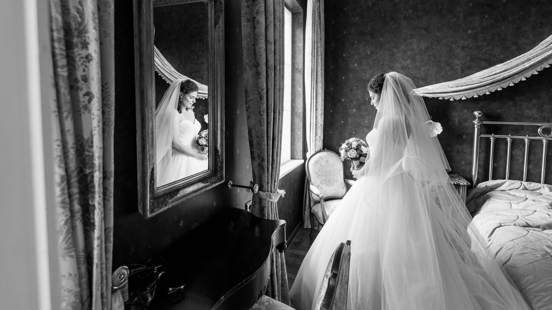 Braut in Kleid vor Fenster in Schwarz-Weiß