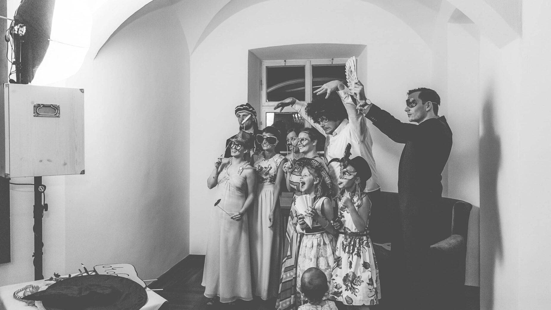 Feiernde Hochzeitsgäste beim Photobooth mit Verkleidung